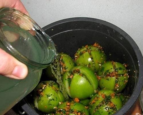 Квашеные зелёные помидоры с чесноком и зеленью в кастрюле