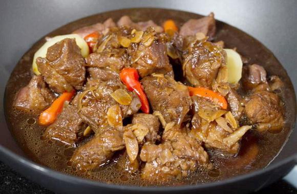 Говядина тушёная на сковородке с грушей, мёдом и чесноком