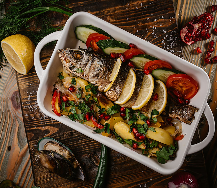 Сибас, фаршированный гремолатой, запеченный с овощами